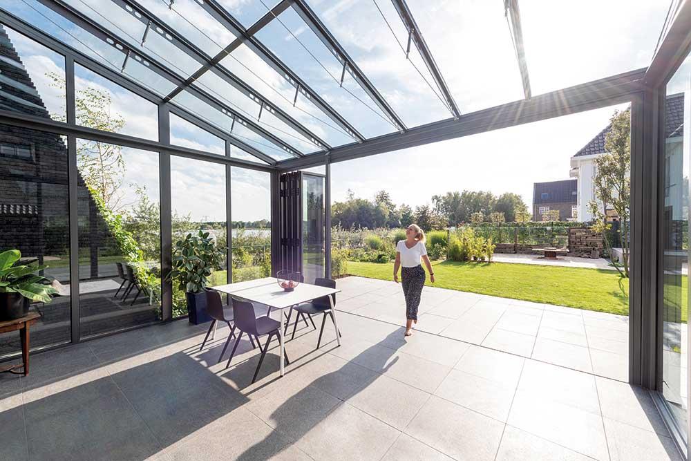 Die Glas-Faltwände lassen sich links und rechts mühelos zur Seite schieben: Der Wintergarten öffnet sich komplett zu Terrasse hin.